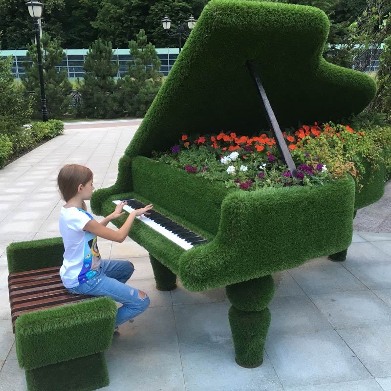child playing a wonderful outside grand piano covered in artificial grass