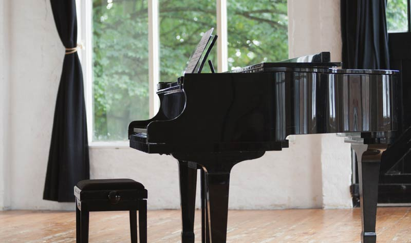 grand piano and stool in a rehearsal studio