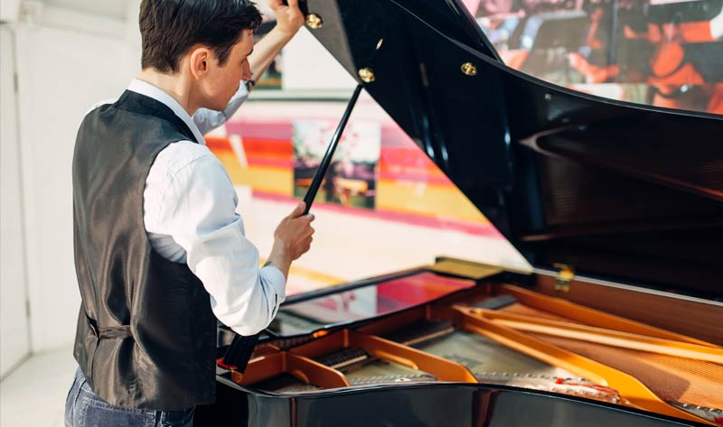 man opens the lid of black grand piano