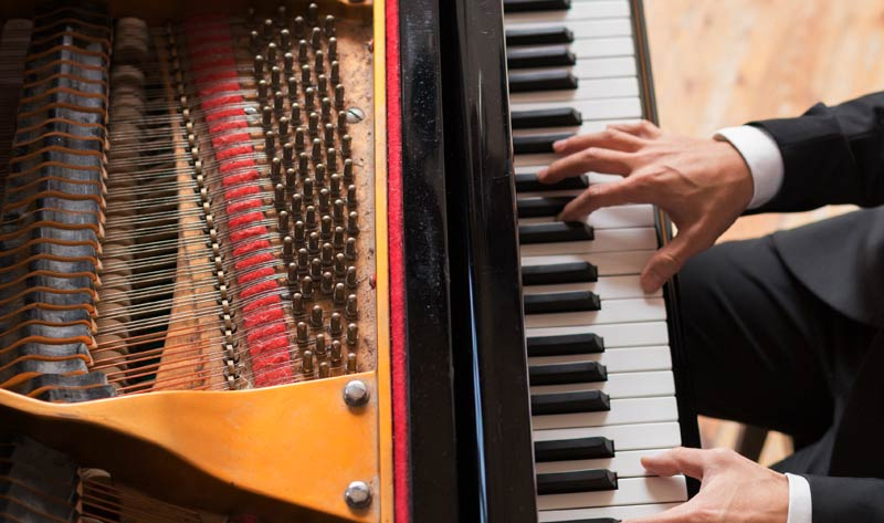 man playing on a grand piano in a rehearsal studio