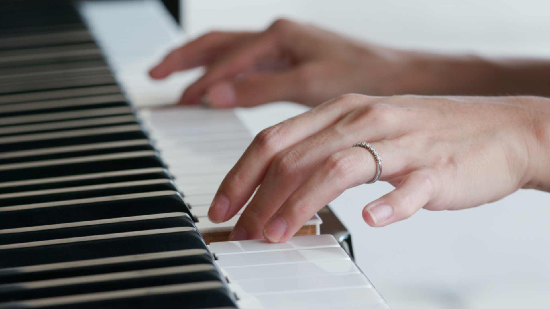 womans hand playing a piano background